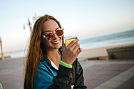 Young woman drinking beer by the sea - KIJF000433