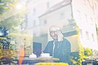 Businessman in a cafe behind windowpane - MAEF011818