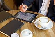Businessman sitting in a coffee shop using digital tablet, partial view - MAEF011824