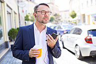 Portrait of businessman with coffee to go wearing earphones - MAEF011833