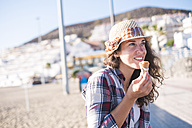 Young woman eating ice cream on the beach - SIPF000548