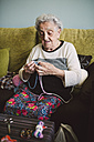 Portrait of crocheting senior woman sitting on couch at home - RAEF001203