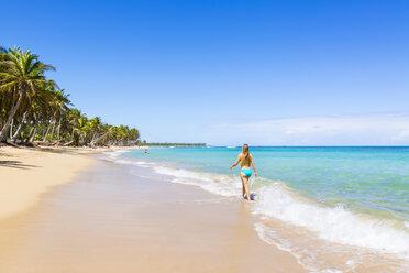 Dominican Rebublic, Young woman walking along tropical beach - HSIF000454
