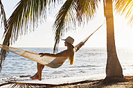Dominican Rebublic, Young woman in hammock looking out over tropical beach - HSIF000463