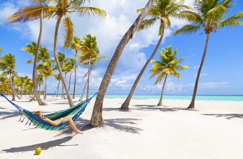 Dominican Rebublic, Young woman lying in hammock on tropical beach - HSIF000478