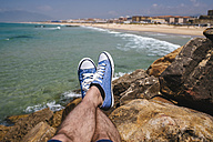 Spain, Andalusia, Tarifa, Close-up of sneakers on stones - KIJF000441