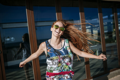Portrait of laughing redheaded young woman with mirrored sunglasses - KIJF000459