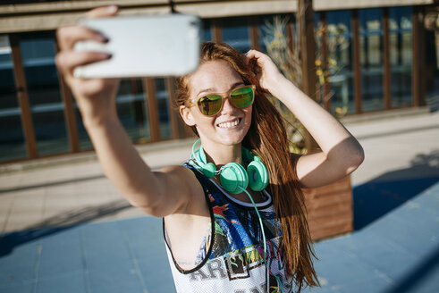 Smiling young woman wearing mirrored sunglasses taking selfie with smartphone - KIJF000462