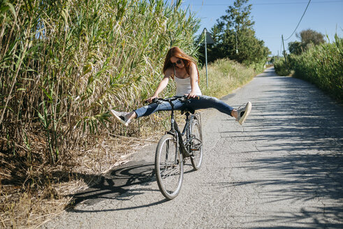 Playful young woman riding bicycle on country lane - KIJF000483