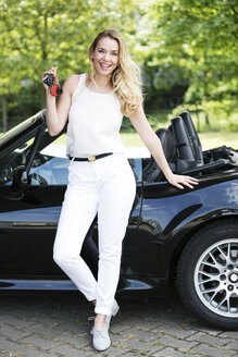 Portrait of smiling blond woman with car keys in front of black sports car - GDF001011