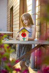 Portrait of girl with painted birdhouse - SARF002772
