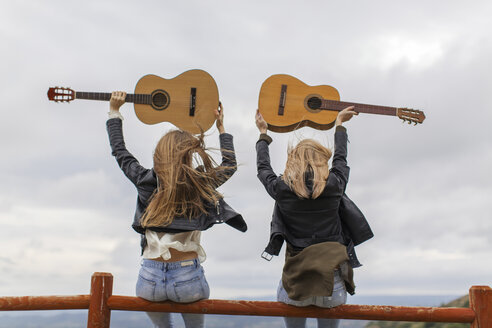 Two women sitting on wooden fence lifting up guitars - JPF000159