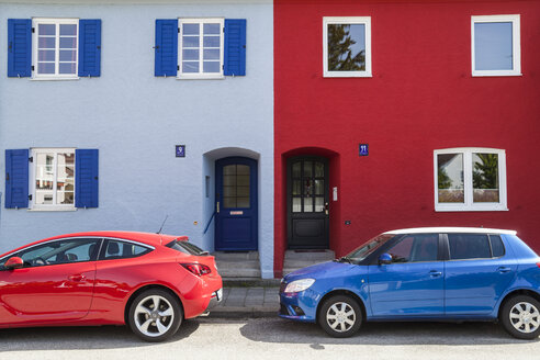 A red and a blue car parking in front of a blue and a red house - TCF004971