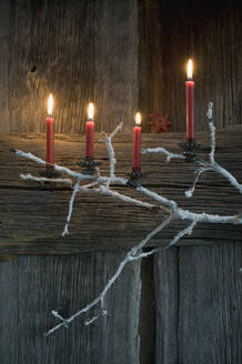 Four lighted Advent candles on twig in front of wooden wall - ASF005903