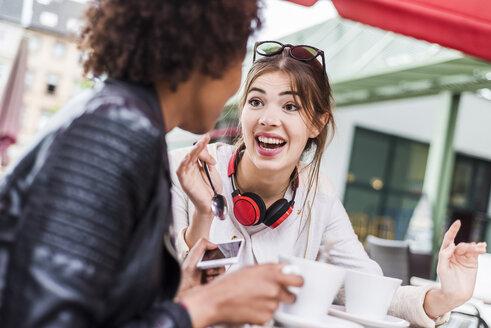 Two best friends talking in a cafe - UUF007643