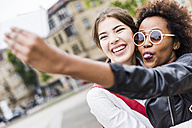 Portrait of two happy best friends taking selfie with smartphone - UUF007658