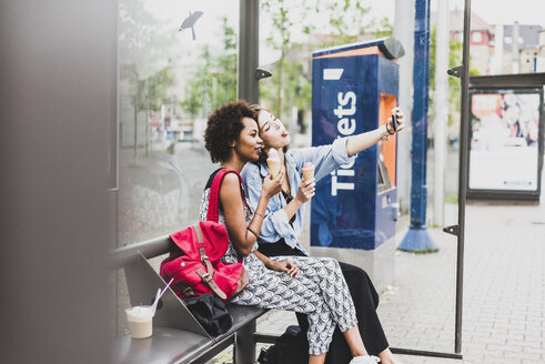Two women with icecream cones sitting at bus stop taking selfie with smartphone - UUF007670