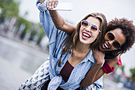 Portrait of two happy best friends taking selfie with smartphone - UUF007679