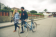 Couple with bicycle and skateboard walking on the street - DAPF000118