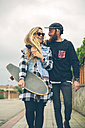 Happy couple with skateboard walking on pavement - DAPF000121