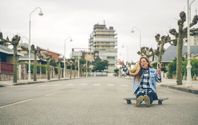 Carefree young woman listening to music sitting on skateboard - DAPF000130