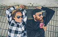 Smiling couple lying on skateboard - DAPF000139