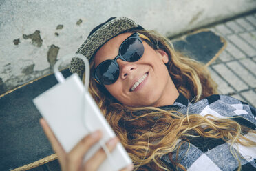 Smiling young woman lying on skateboard looking at cell phone - DAPF000142