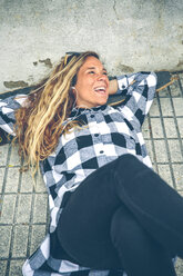 Happy young woman lying on skateboard listening music with earphones - DAPF000145