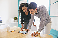 Young businessman and woman looking at digital tablet in office - EBSF001462