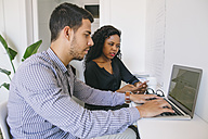 Young businessman and woman working together in office, using laptop - EBSF001465