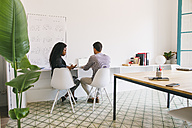 Two young business people working in office - EBSF001468