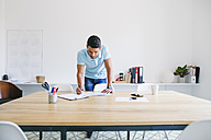 Young businessman standing at desk looking trough files - EBSF001540