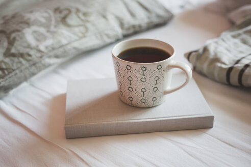 Book and cup of black coffee on a bed - ASCF000621