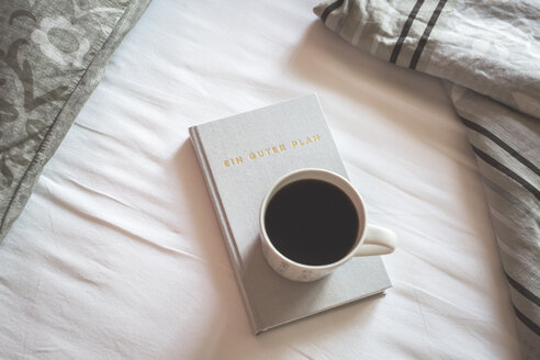 Book and cup of black coffee on a bed - ASCF000624