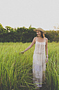 Smiling woman wearing summer dress and hat in nature - KNTF000346