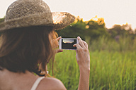 Back view of woman taking picture with smartphone in nature - KNTF000349