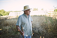 Portrait of a farmer with hatchet looking at distance - RAEF001218