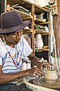 Potter in workshop working on earthenware jar - KNTF000353