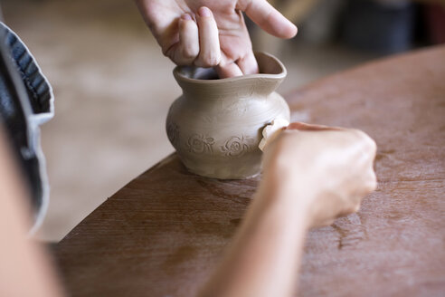 Potter in workshop working on earthenware jar - KNTF000359