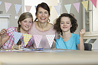 Happy mother and daughters with paper garland - NHF001492