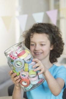 Girl holding jar with masking tape - NHF001495