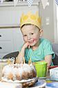 Happy boy wearing paper crown sitting at birthday table - NHF001501