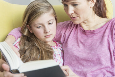 Mother and daughter reading a book together - NHF001510
