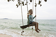 Young girl on beach, sitting on swing in Thailand - SBOF000048