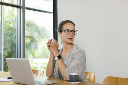 Woman at table with cup of coffee and laptop - SBOF000063
