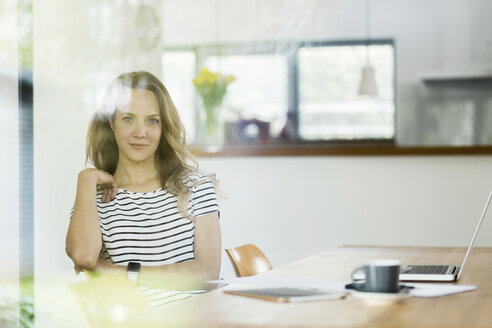 Portrait of confident woman with laptop at table - SBOF000075