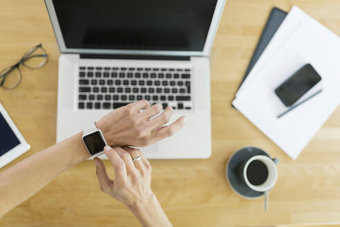 Woman with smartwatch and laptop at desk - SBOF000081