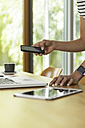 Woman at table with cell phone, laptop and digital tablet - SBOF000084
