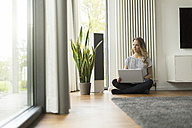 Woman at home sitting on floor with laptop - SBOF000087
