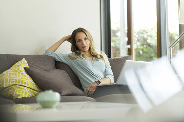 Woman at home sitting on couch with laptop - SBOF000093